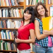 Beautiful female students in a library — Stock Photo