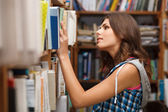 Beautiful female student in a library — Stok fotoğraf