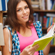 Beautiful female student in a library - Stockfoto