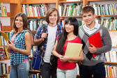 Group of students in a library — Stock Photo