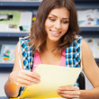 Beautiful female student in a library - Foto Stock