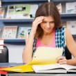 Stressed female student in a library - Stockfoto