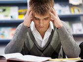 Estudante do sexo masculino bonito em uma biblioteca — Foto Stock
