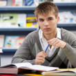 Handsome male student in a library — Stock Photo