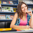 Beautiful female student in a library — Stock Photo