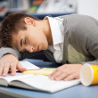 Tired student sleeping at the desk — Stockfoto