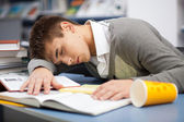 Tired student sleeping at the desk — Stock Photo