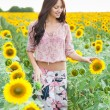 Beautiful lady walking in sunflower field — Stock Photo