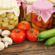 Stock Photo: Fresh and canned vegetables on wooden table