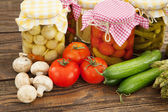 Fresh and canned vegetables on a wooden table — Stock Photo