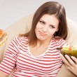Photo: Slim woman choosing between a salad and hamburger