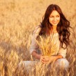 Beautiful brunette lady in wheat field at sunset - Stok fotoğraf