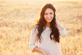 Beautiful brunette lady in wheat field at sunset — Stock Photo