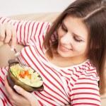 Beautiful young woman eating a salad — Stock Photo