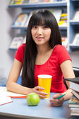 Beautiful female student in a university library — Stockfoto