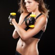 Slim woman with dumbbells — Stock Photo #19776095