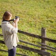 Female photographer shooting in open air - Stock Photo