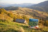 Berglandskap med en målning på förgrunden — Stockfoto