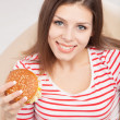 Woman eating a hamburger — Stock Photo