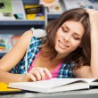 Beautiful female student in a university library — Stock Photo