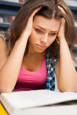 Stressed female student in a university library — Stock Photo