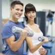 Cheerful young couple in a gym — Stock Photo