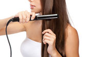 Young woman iwth a hair straightener — Stock Photo