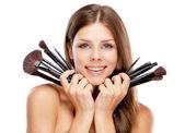 Beautiful woman holding makeup brushes — Stock Photo