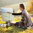 Young artist painting an autumn landscape — Stock Photo #35504651