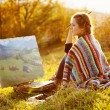 Young artist painting an autumn landscape — Stock Photo #35504711