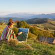 Young artist painting an autumn landscape — Stock Photo #35906375