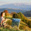 Young artist painting an autumn landscape — Stock Photo