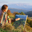 Stock Photo: Young artist painting an autumn landscape