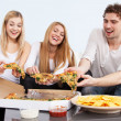 Group of young people eating pizza at home — Stock Photo #38208679