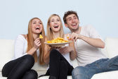 Group of young people eating pizza at home — Stock Photo