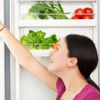 Young woman looking into a refrigerator — Stok fotoğraf