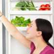 Young woman looking into a refrigerator — Stock fotografie