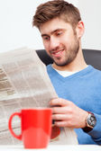 Young man reading a newspaper — Stock Photo
