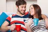 Young couple drinking coffee at home — Stock Photo