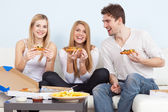 Group of young people eating pizza at home — Stok fotoğraf