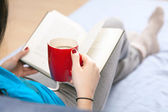 Woman reading a book in bed — Stock Photo
