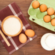 Eggs, milk and flour on a wooden table — Stock Photo
