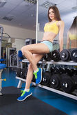 Young slim woman exercising in a gym — Stok fotoğraf