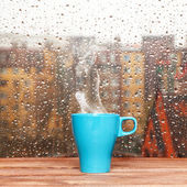 Steaming coffee cup on a rainy day window background — Photo