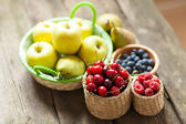 Fresh juicy apples, pears and berries on a wooden table — Stock Photo