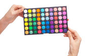Female hand holding a makeup palette, white background — ストック写真