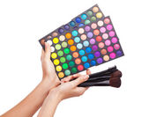 Female hand holding a makeup palette, white background — Stok fotoğraf