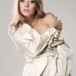 Beautiful fashion model seductively posing in beige coat — Stock Photo #5727475
