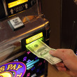 Hand putting money into slot machine in Las Vegas - Stock Photo
