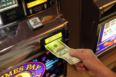 Hand putting money into slot machine in Las Vegas — Stock Photo